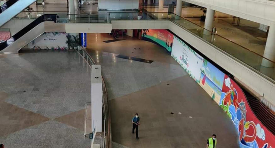 Two men are seen walking inside Bali Airport as it remains largely empty.