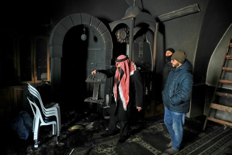 Palestinians inspect the damage from an apparent arson attack on a mosque in Israeli-occupied east Jerusalem