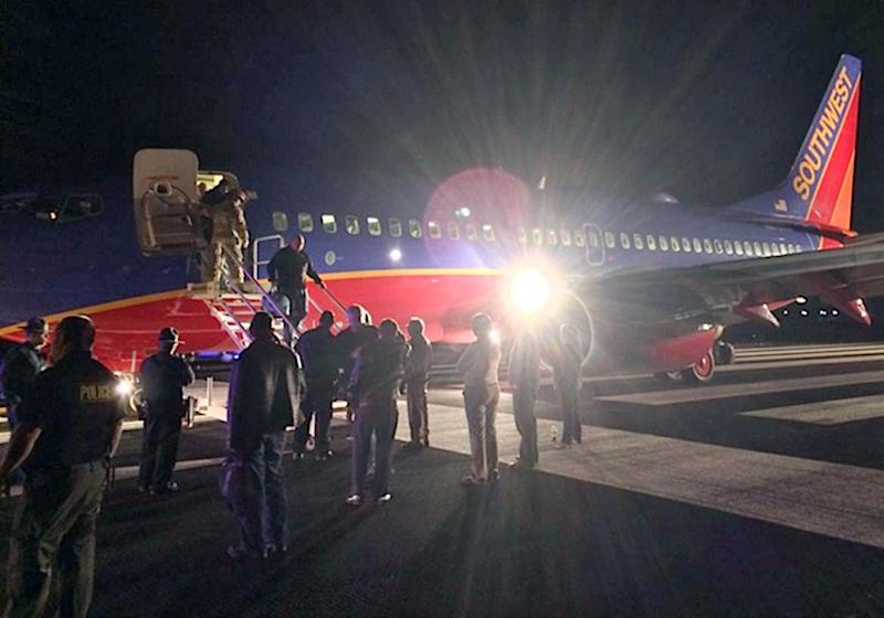 In this Sunday, Jan. 12, 2014 photo provided by Scott Schieffer, passengers exit a Southwest Airlines flight that was supposed to land at Branson Airport in Branson, Mo., but instead landed at Taney County Airport, in Hollister, Mo., that only has about half as much runway. A Southwest spokesman said all 124 passengers and five crew members were safe. (AP Photo/ Scott Schieffer) MANDATORY CREDIT