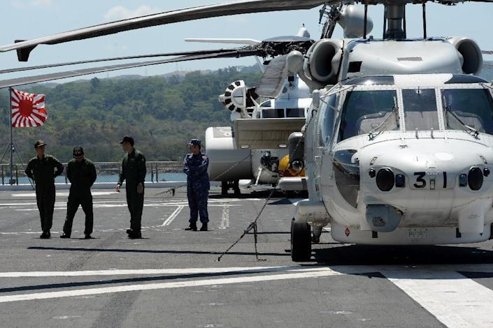 Helicopter crew members of the Japanese helicopter carrier Ise stand on the deck shortly after arriving at the former US naval base, Subic port, north of Manila, on April 26, 2016 (AFP Photo/Ted Aljibe)