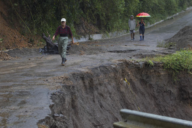 <p>Neighbors walk under the rain past a washed out road in Alajuelita on the outskirts of San Jose, Costa Rica, Thursday, Oct. 5, 2017. (Photo: Moises Castillo/AP) </p>