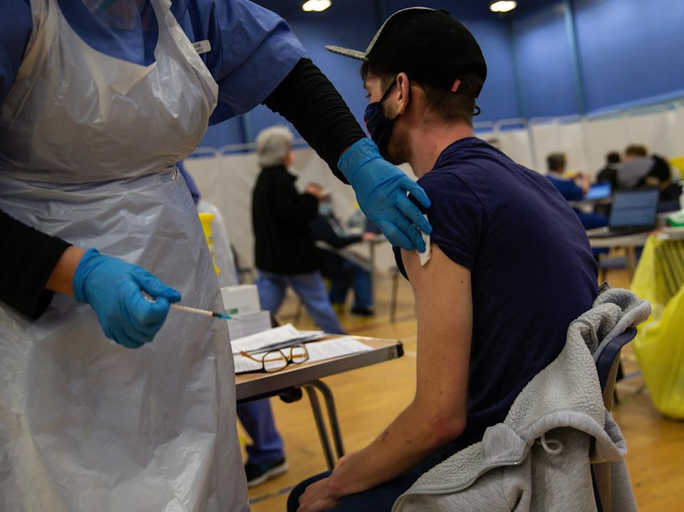 CWMBRAN, WALES - DECEMBER 29:  A general view of a NHS worker as he receives his first dose of the Pfizer/BioNTech vaccine in the waiting area for any adverse reactions on December 29, 2020 in Cwmbran, Wales. Various locations across United Kingdom were designated as covid-19 vaccine hubs. NHS staff, over-80s, will be among the first to receive the Pfizer/BioNTech vaccine, which recently received approval from the country's health authorities. It is anticipated that the Oxford University Vaccine will be approved within the next few days. (Photo by Huw Fairclough/Getty Images)