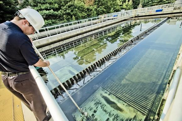 Worker with hard hat probing a water treatment plant collection pool.