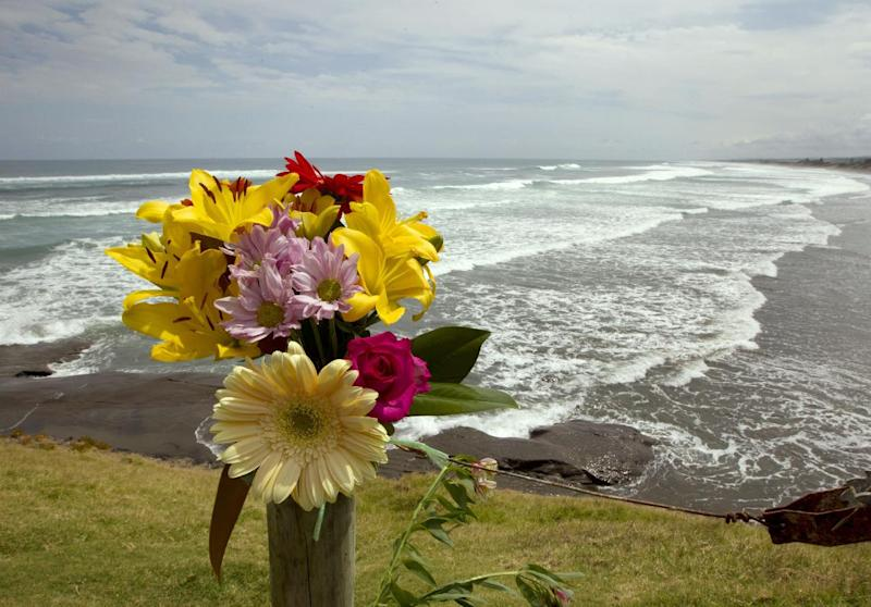 A flower tribute sits on a fence post as a memorial at Muriwai Beach near Auckland, New Zealand, Thursday, Feb. 28, 2013, a day after Adam Strange was killed by a shark. About 150 friends and family of Strange, 46, wrote messages to him in the sand and stepped into the water Thursday at a New Zealand beach to say goodbye after he was killed Wednesday by a large shark. (AP Photo/New Zealand Herald, Brett Phibbs) New Zealand Out, Australia Out