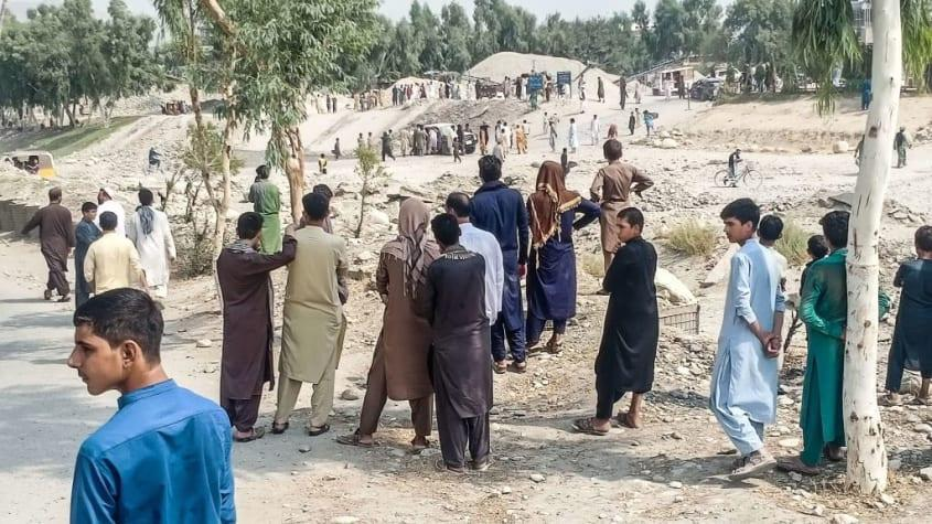 Residents of Jalalabad and Taliban fighters look at the scene of a bombing.