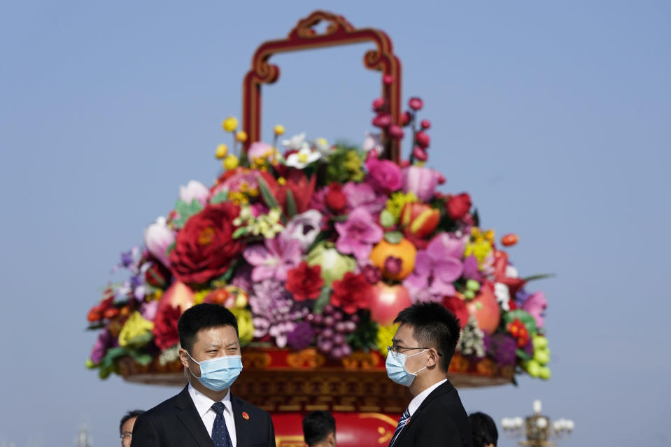 Attendees wear masks to protect from the coronavirus as they chat near a giant floral decoration setup for the Oct. 1 National Day holidays during a ceremony to mark Martyr's Day at Tiananmen Square in Beijing on Wednesday, Sept. 30, 2020. (AP Photo/Ng Han Guan)