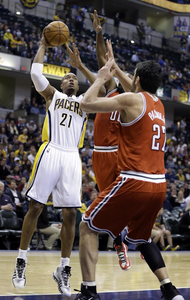 Indiana Pacers forward David West, left, shoots over Milwaukee Bucks guard O.J. Mayo, center, and center Zaza Pachulia in the second half of an NBA basketball game in Indianapolis, Friday, Nov. 15, 2013. The Pacers defeated the Bucks 104-77. (AP Photo/Michael Conroy)