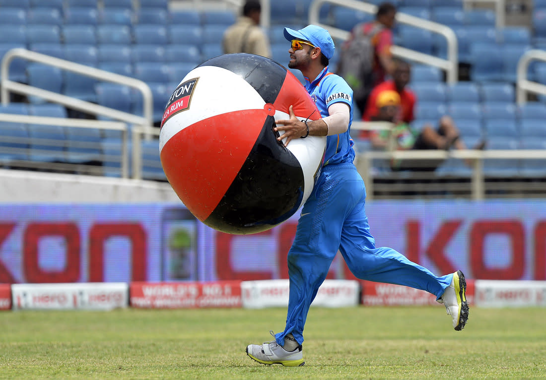 Indian cricket team's acting captain Virat Kohli removes a plastic ball from the ground during the third match of the Tri-Nation series between India and Sri Lanka at the Sabina Park stadium in Kingston on July 2, 2013. Indian won the toss and elected to filed first. AFP PHOTO/Jewel Samad