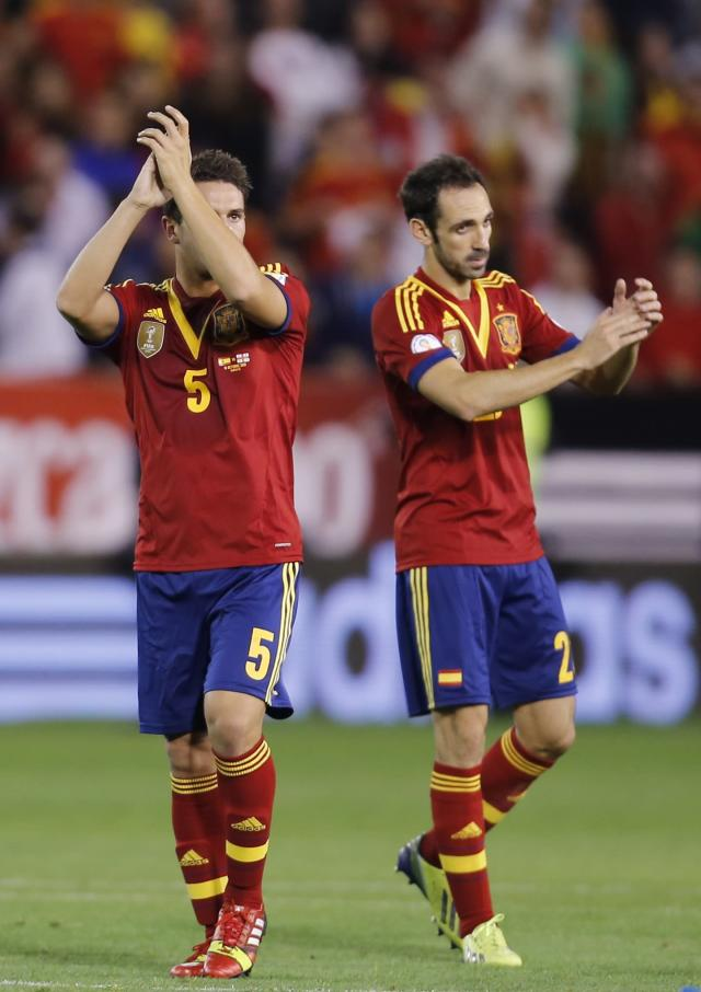 Spain's Koke, left, and Juanfran celebrate their qualification for the 2014 World Cup at the end of their Group I qualifying soccer match against Georgia at the Carlos Belmonte stadium in Albacete, Spain, Tuesday Oct. 15, 2013. (AP Photo/Fernando Bustamante)