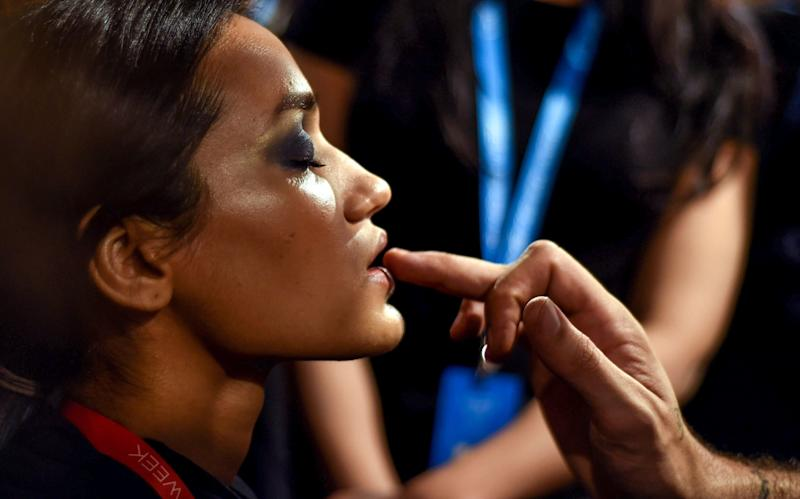 An Indian model gets ready with the makeup and hair backstage crew before the show begins at the Lakmé Fashion Week (LFW) Summer Resort 2019, in Mumbai on January 31, 2019. (Photo by Sujit JAISWAL / AFP) (Photo credit should read SUJIT JAISWAL/AFP/Getty Images)