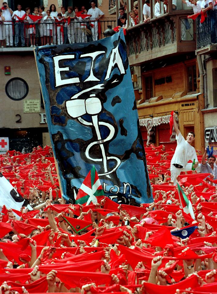 FILE PHOTO: Thousands of people hold their bandanas moments before the official opening of the week-long San Fermin festival  as supporters of Basque Separatists supporting the organization ETA display a banner in Pamplona, Spain, July 6, 1996.  REUTERS/Desmond Boylan/File photo