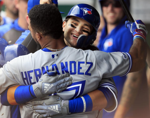 Toronto Blue Jays' Bo Bichette, back, hugs teammate Teoscar Hernandez (37) after his solo home run during the eighth inning of a baseball game against the Kansas City Royals at Kauffman Stadium in Kansas City, Mo., Wednesday, July 31, 2019. (AP Photo/Orlin Wagner)