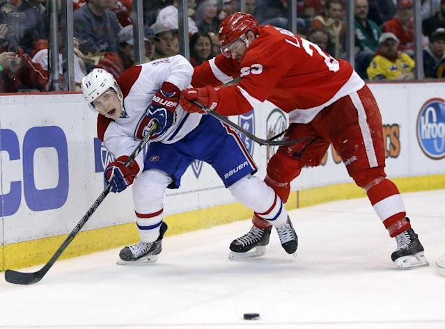 Detroit Red Wings' Brian Lashoff, right, shoves Montreal Canadiens' Brendan Gallagher (11) off the puck during the second period of an NHL hockey game Thursday, March 27, 2014, in Detroit. (AP Photo/Duane Burleson)