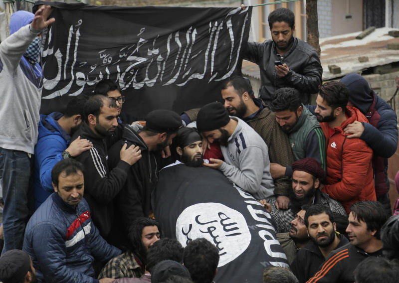 Kashmiri Muslims mourn near the body of local rebel Mugees Ahmad Mir during his funeral on the outskirts of Srinagar, India, Saturday, Nov. 18, 2017. The body of Mir was recovered from the area hours after a rebel attack left a police officer dead on the outskirts of Srinagar on Friday, police said. The writing on banner is a verse from the Quran. (AP Photo/Mukhtar Khan)