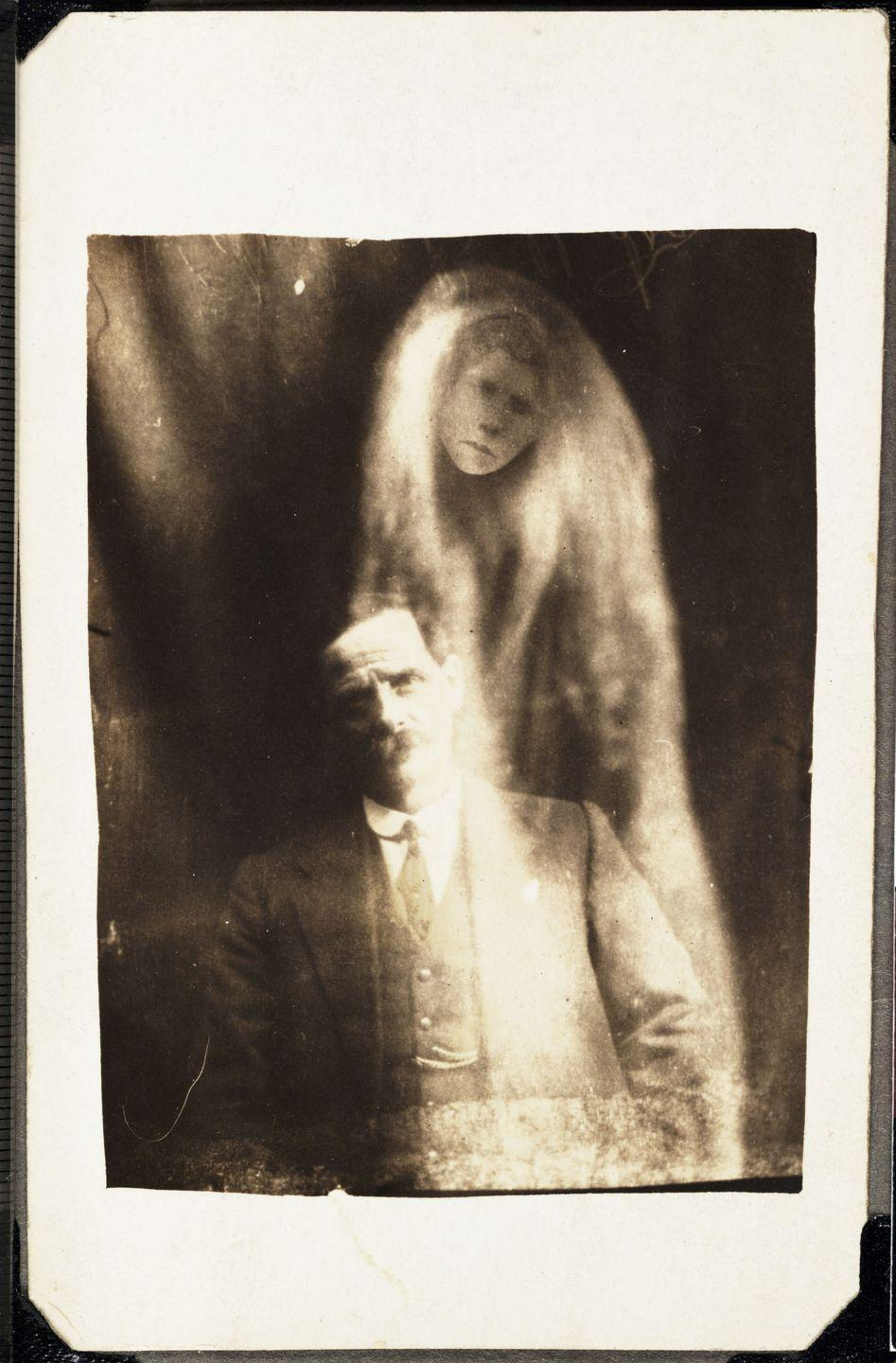 <p>The image of a man's deceased second wife floats above him in a photo taken shortly after performing a seance. </p>