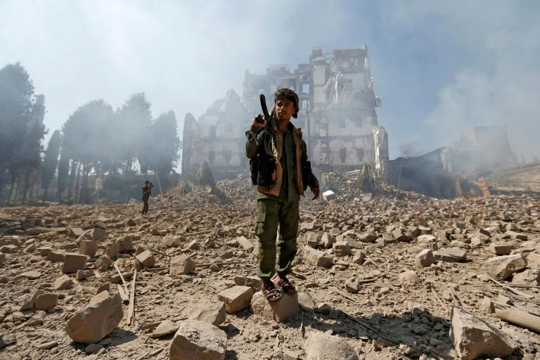 Yemeni Huthi rebel fighters inspect the damage after a reported Saudi-led coalition air strike hit presidential palace in the capital Sanaa on December 5, 2017