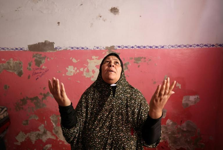A Palestinian woman prays after her family house got damaged by an Israeli air strike in Jabaliya, in the northern Gaza Strip, on May 20, 2021