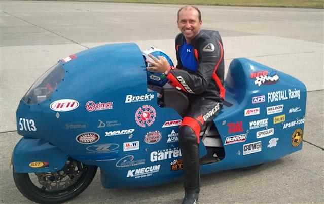 In this 2011 photo provided by the Loring Timing Association the late Bill Warner, 44, of Wimauma, Fla., holds his helmet while sitting on a motorcycle. Officials say Warner, who died Sunday at an annual speed trial event in northern Maine, lost control and crashed while trying to top 300 mph. Race Director Tim Kelly says Warner was clocked at 285 mph before he lost control. (AP Photo/Loring Timing Association)