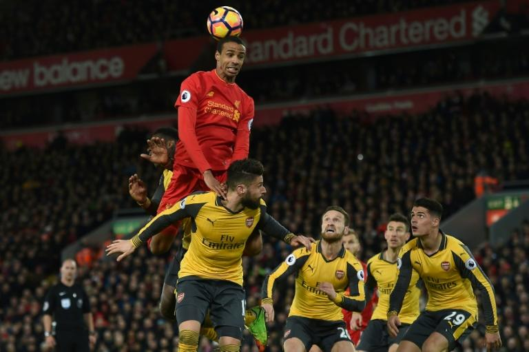 Liverpool's Joel Matip jumps to win a header as Arsenal's players look on during their match on March 4, 2017