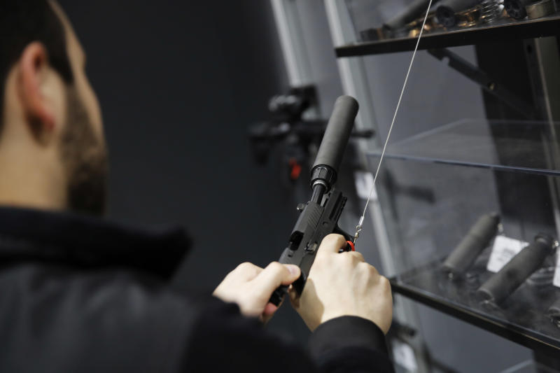 A visitor pulls the slide of a pistol with a silencer at a National Rifle Association outdoor sports trade show on Feb. 10, 2017, in Harrisburg, Pennsylvania.