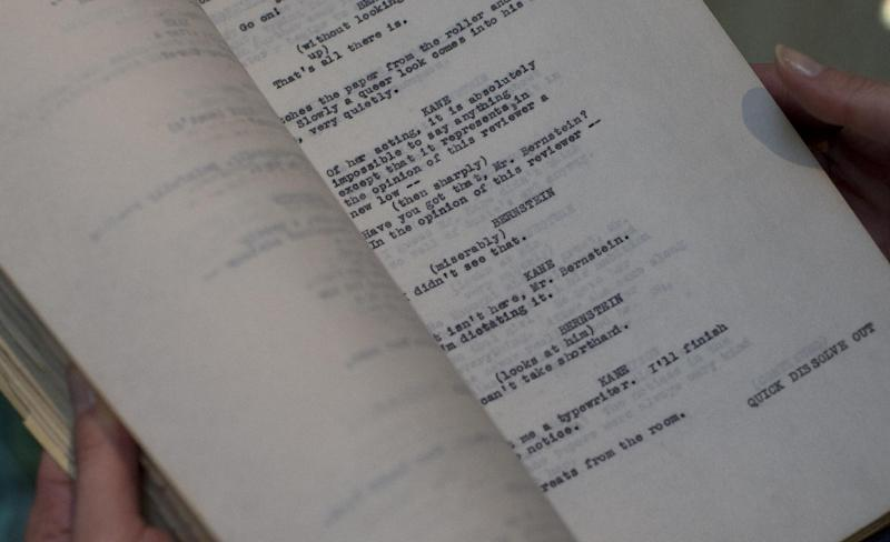 "A page of the originally titled 'American' or as it is now known 'Citizen Kane' film which was Orson Well working copy of the script held by an employee of Sotheby's auction house in London, Thursday, Feb. 27, 2014. Orson Welles' personal draft script for ""Citizen Kane"" is up for sale _ from the collection of an American almost as wealthy as the movie's monstrous newspaper mogul, though considerably more private. The script, which has an estimated price of 15,000 pounds to 20,000 pounds ($25,000 to $33,000), is part of a sale of more than 1,000 items owned by the late Stanley Seeger, an affluent collector of everything from Old Masters and contemporary art to historical oddities.(AP Photo/Alastair Grant)"