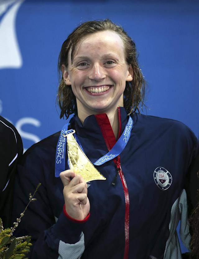 Katie Ledecky of the U.S. smiles as she poses with her gold medal after she set a new world record in her women's 1500m freestyle final at the Pan Pacific swimming championships in Gold Coast, Australia, Sunday, Aug. 24, 2014. Ledecky won the race setting a new world record of 15 minutes, 28.36 seconds.(AP Photo/Rick Rycroft)