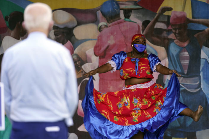 Dancers perform as Democratic presidential candidate former Vice President Joe Biden watches during a visit Little Haiti Cultural Complex, Monday, Oct. 5, 2020, in Miami. (AP Photo/Andrew Harnik)