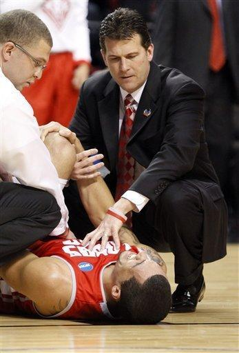 New Mexico coach Steve Alford, right, comforts forward Drew Gordon as he holds his knee and grimaces in pain during the first half of their NCAA tournament third-round college basketball game against Indiana in Portland, Ore., Saturday, March 17, 2012. Gordon left the court but returned later in the half. (AP Photo/Don Ryan)