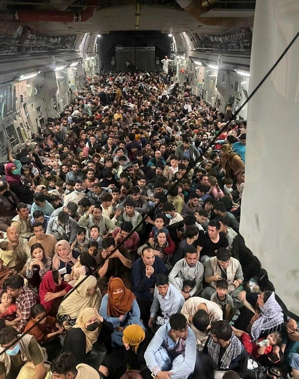 Hundreds of Afghan citizens are evacuated on a US air force plane from Hamid Karzai International Airport on Sunday (EPA)