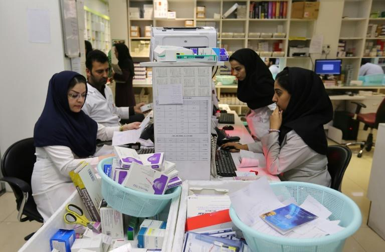 """Iranian medical staff at the state-run """"13 Aban"""" pharmacy in Tehran -- hordes of patients queue patiently for hours as the dispensary stocks and subsidises medicines for rare diseases (AFP Photo/ATTA KENARE)"""