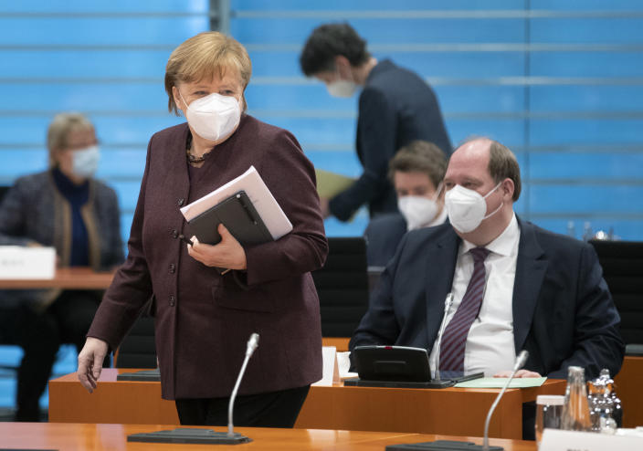 FILE - In this file photo dated Wednesday, Feb. 10, 2021, German Chancellor Angela Merkel, front left, walks past Helge Braun, Head of the Chancellery, right, as she arrives for the weekly cabinet meeting in Berlin, Germany. Slow off the blocks in the race to immunize its citizens against COVID-19, Germany faces the problem of having a glut of vaccines and not enough arms to inject. With its national vaccine campaign lagging far behind that of Israel, Britain and the United States, there are growing calls in this country of 83 million to ditch or rewrite the rulebook. (AP Photo/Michael Sohn, FILE)