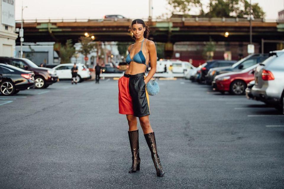 <p>Model Nakisa Kachingwe wears a blue denim bikini top, red and black leather shorts, black see-through heeled boots, and carries a small baby blue fuzzy purse outside the Collina Strada show.</p>