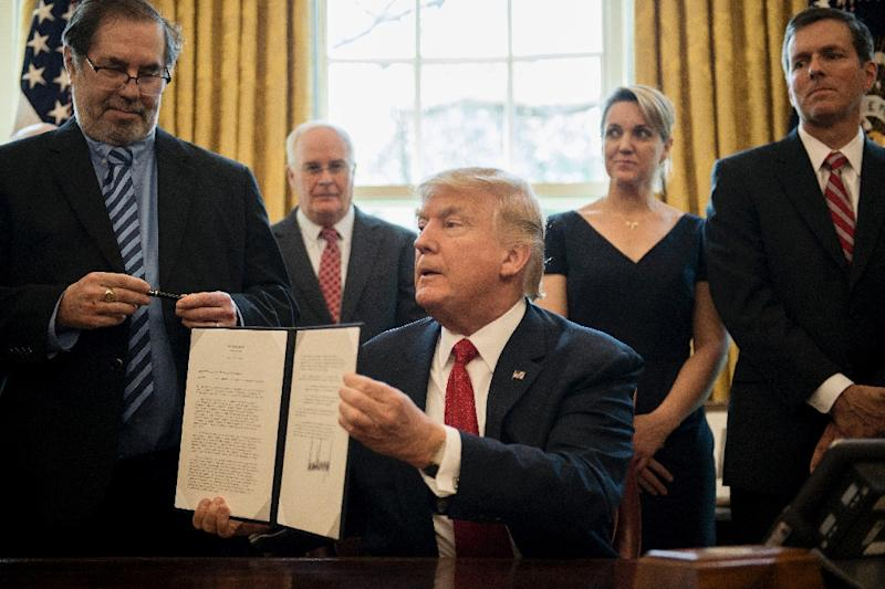 US President Donald Trump (C) signs the Memorandum Regarding the Investigation Pursuant to Section 232(B) of the Trade Expansion Act at the White House
