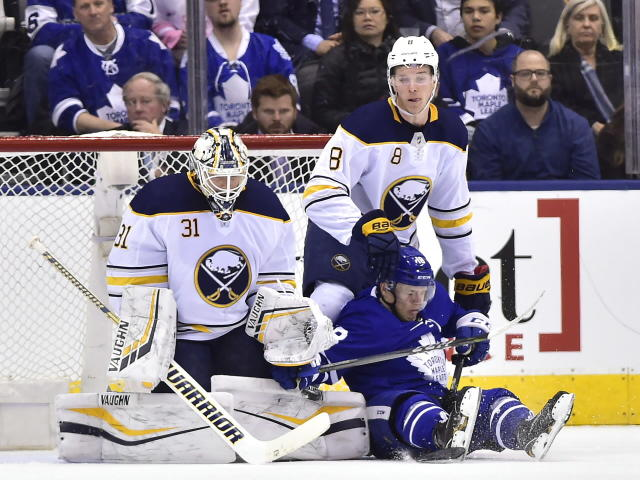Buffalo Sabres defenseman Casey Nelson (8) takes down Toronto Maple Leafs left wing Andreas Johnsson (18) as Sabres goaltender Chad Johnson (31) prepares to make a save during first period NHL hockey action in Toronto on Monday, March 26, 2018. (Frank Gunn/The Canadian Press via AP)