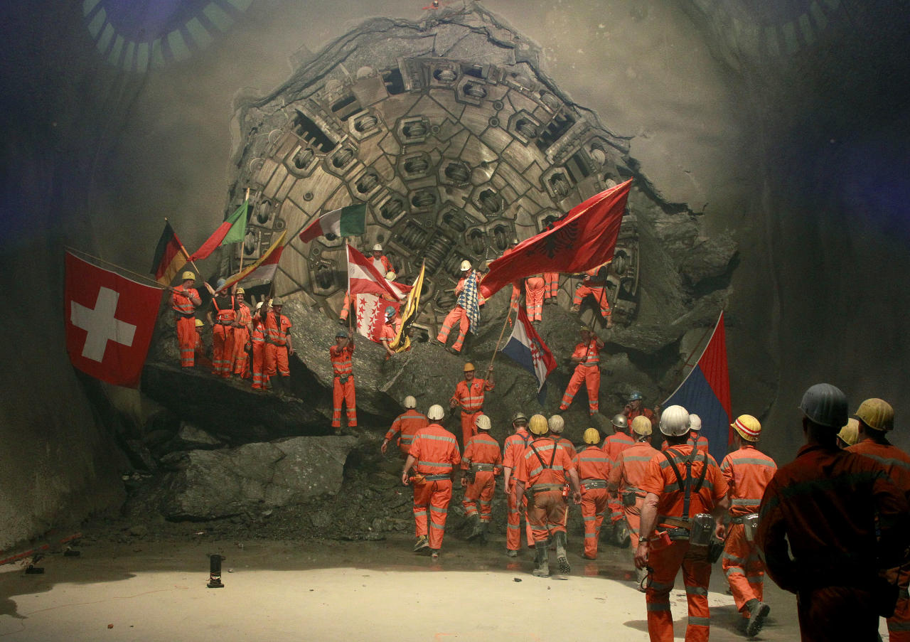 Miners wave with the flags of their home countries as they celebrate after a giant drill machine broke through the rock at the final section Sedrun-Faido, at the construction site of the NEAT Gotthard Base Tunnel March 23, 2011. Crossing the Alps, the world's longest train tunnel should become operational at the end of 2016. The project consists of two parallel single track tunnels, each of a length of 57 km (35 miles).  REUTERS/Arnd Wiegmann (SWITZERLAND - Tags: BUSINESS TRAVEL EMPLOYMENT) - RTR2KAQH