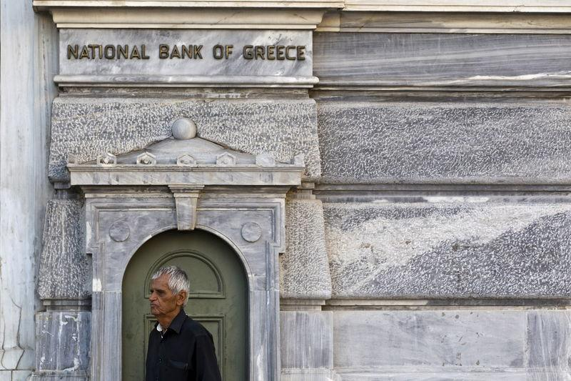 A man stands as he waits outside a National Bank branch to open in Athens