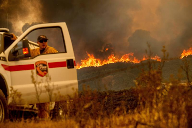 The Ranch fire, part of the Mendocino Complex fire, crests a ridge as Battalion Chief Matt Sully directs firefighting operations on High Valley Road near Clearlake Oaks, California, on Sunday. (NOAH BERGER via Getty Images)