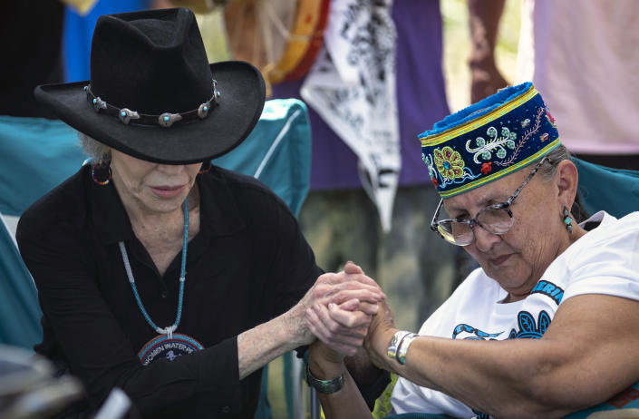"""FILE - In this June 7, 2021, file photo, actress and activist Jane Fonda, left, locks hands with Grandmother Mary Lyons after they prepared to perform a traditional water ceremony, on Monday, June 7, 2021, in Clearwater County, Minn. More than 2,000 Indigenous leaders and """"water protectors"""" gathered in Clearwater County from around the country to protest the construction of Enbridge Line 3. Enbridge Inc. announced Wednesday, Sept. 29, 2021, that the upgrade and expansion of its Line 3 pipeline across Minnesota is complete and will become operational on Friday, Oct. 1. (Alex Kormann/Star Tribune via AP, File)"""