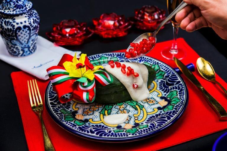 The traditional chile en nogada features poblano chile peppers bathed in creamy white sauce and topped with red pomegranate seeds