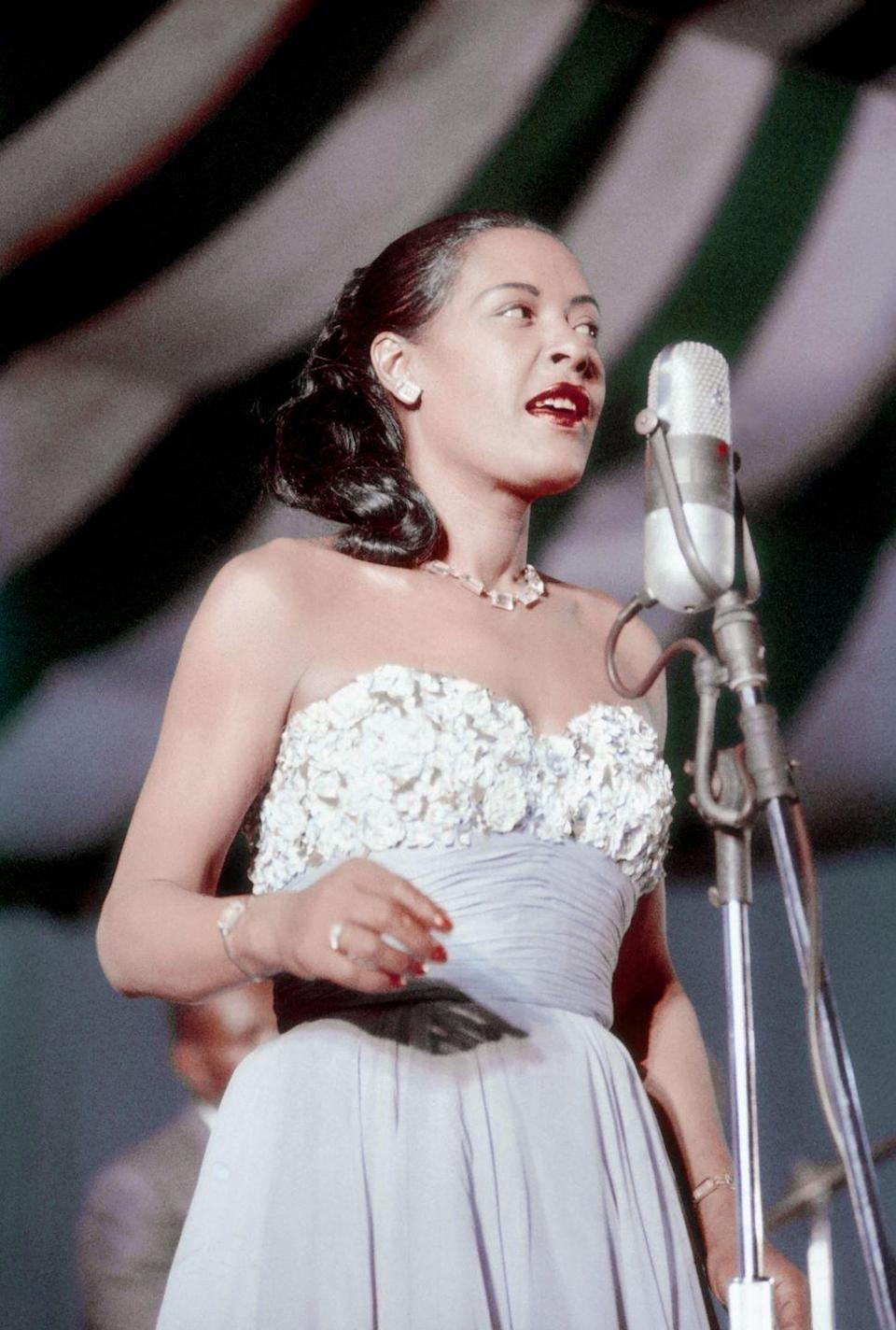 <p>Music legend Billie Holiday performing in a strapless powder-blue gown with an embellished bodice and a bright-red lip.</p>