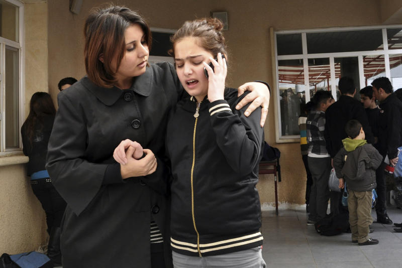 A woman comforts her daughter in a schoolyard after a fatal shooting of an American gym teacher at a school in Sulaimaniyah, 160 miles (260 kilometers) northeast of Baghdad, Iraq, Thursday, March, 1, 2012. An American gym teacher was killed Thursday when a student in a crowded classroom pulled out a gun, shot the teacher and then shot himself, officials and eyewitnesses said. (AP Photo/Yahya Ahmed)