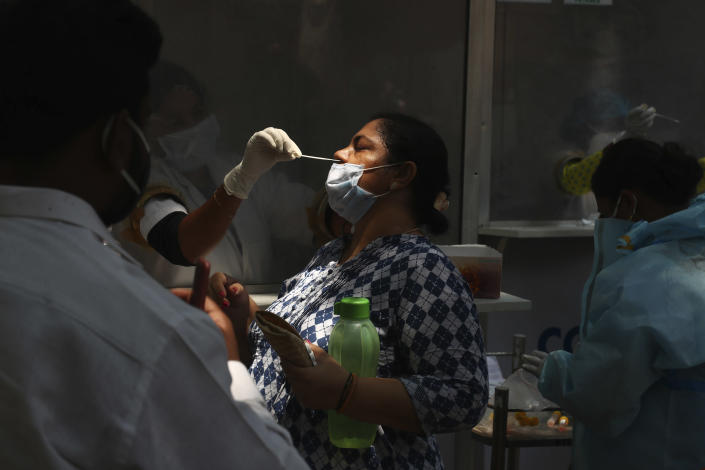 A health worker takes a nasal swab sample of a woman to test for COVID-19 in Hyderabad, India, Monday, May 3, 2021. COVID-19 infections and deaths are mounting with alarming speed in India with no end in sight to the crisis. People are dying because of shortages of bottled oxygen and hospital beds or because they couldn't get a COVID-19 test. (AP Photo/Mahesh Kumar A.)