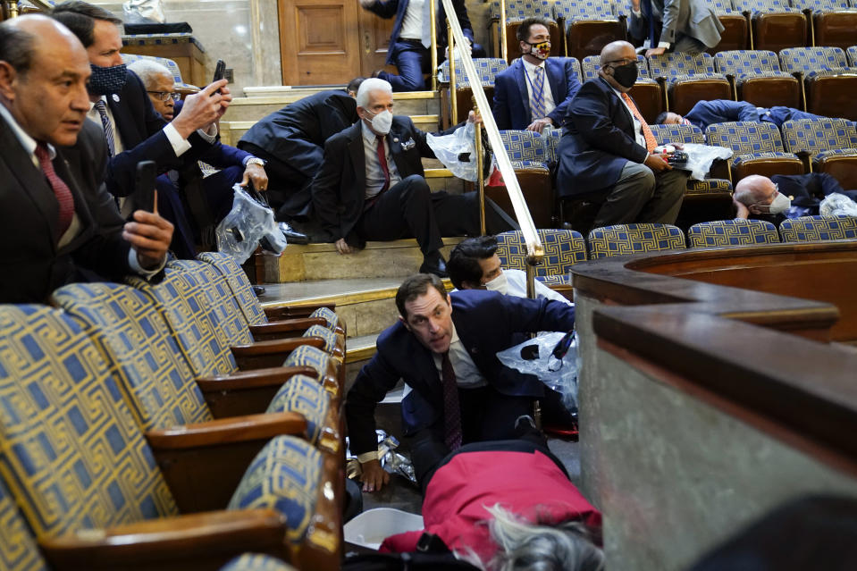 FILE - In this Jan. 6, 2021, file photo people shelter in the House gallery as rioters try to break into the House Chamber at the U.S. Capitol. Arguments begin Tuesday, Feb. 9, in the impeachment trial of Donald Trump on allegations that he incited the violent mob that stormed the U.S. Capitol on Jan. 6. (AP Photo/Andrew Harnik, File)