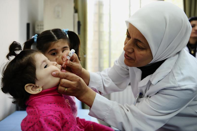 In this photo released by UNICEF, a health worker administers polio vaccine to a child as part of a UNICEF-supported vaccination campaign at the Abou Dhar Al Ghifari Primary Health Care Center in Damascus, Syria, Tuesday, Oct. 29, 2013. The U.N.'s health agency said Tuesday it has confirmed 10 polio cases in northeast Syria, the first confirmed outbreak of the diseases in the country in 14 years, with a risk of spreading across the region. (AP Photo/UNICEF, Omar Sanadiki)