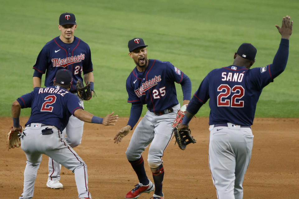 Minnesota Twins players Luis Arraez (2) Trevor Larnach (24), Byron Buxton (25) and Miguel Sano (22) celebrate their victory over the Texas Rangers in a baseball game Saturday, June 19, 2021, in Arlington, Texas. (AP Photo/Michael Ainsworth)