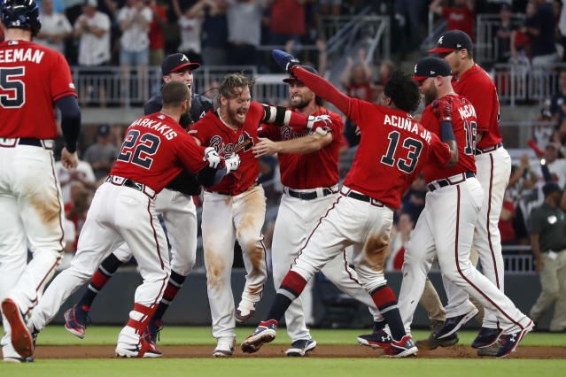 Atlanta Braves' Josh Donaldson, center, is mobbed by teammates after driving in the winning run with a base hit in the ninth inning of a baseball game against the Washington Nationals, Friday, July 19, 2019, in Atlanta. (AP Photo/John Bazemore)