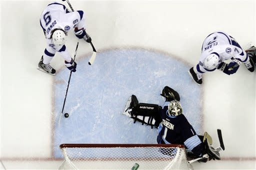 Tampa Bay Lightning's Steve Downie (9) gets the puck behind Pittsburgh Penguins goalie Brent Johnson (1) for his second goal of the first period during an NHL hockey game against the Pittsburgh Penguins in Pittsburgh, Sunday, Feb. 12, 2012. (AP Photo/Gene J. Puskar)