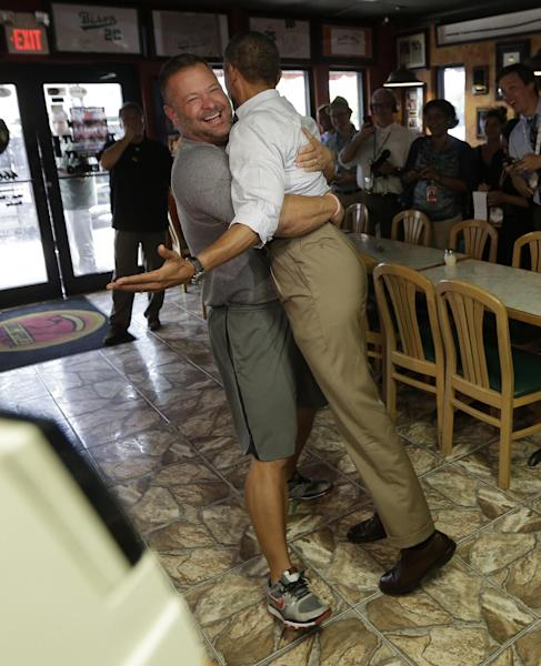 """In this photo taken Sept. 9, 2012, President Barack Obama, right, is set back on the ground by Scott Van Duzer, owner of Big Apple Pizza and Pasta Italian Restaurant in Ft. Pierce, Fla. Obama's handlers let the muscular restaurant owner hoist the president off the ground in a big bear hug during a drop-by visit. """"Look at these guns!"""" Obama enthused about the man's biceps. Every day, the ground troops of Team Obama and Team Romney set out in pursuit of a common goal: winning the day. Everyone poses for the camera. (AP Photo/Pablo Martinez Monsivais)"""