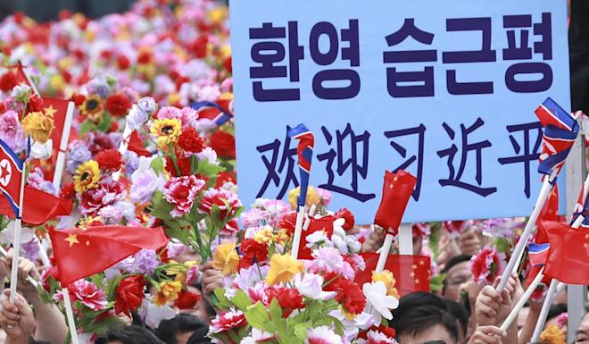 Flowers and flags are used to welcome Xi and his wife Peng Liyuan at Pyongyang's Sunan International Airport about noon on Thursday. Photo: Xinhua