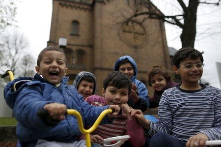 Migrant children from Syria pose in front of a Protestant church in Oberhausen